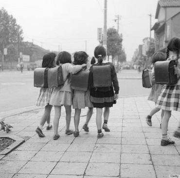 circa 1950:  Japanese schoolchildren on their way to school in Tokyo.  (Photo by Orlando /Three Lions/Getty Images)